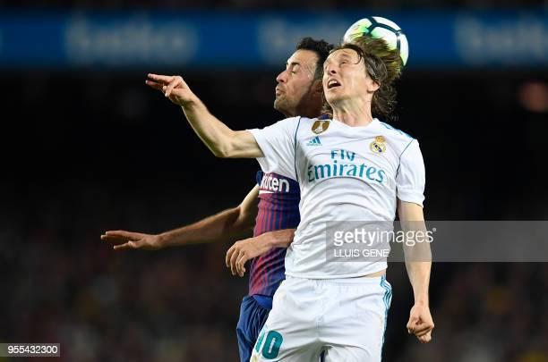 Real Madrid's Croatian midfielder Luka Modric vies with Barcelona's Spanish midfielder Sergio Busquets during the Spanish league football match...