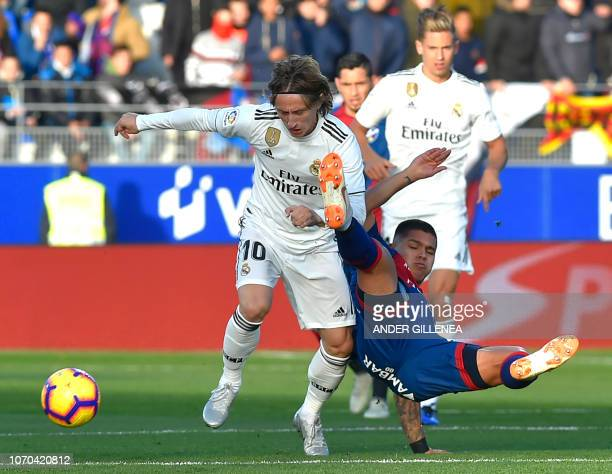 Real Madrid's Croatian midfielder Luka Modric vies with Huesca's Colombian forward Juan Camilo Hernandez during the Spanish league football match...