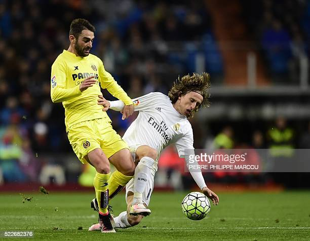 Real Madrid's Croatian midfielder Luka Modric vies with Villarreal's forward Adrian Lopez during the Spanish league football match Real Madrid vs...