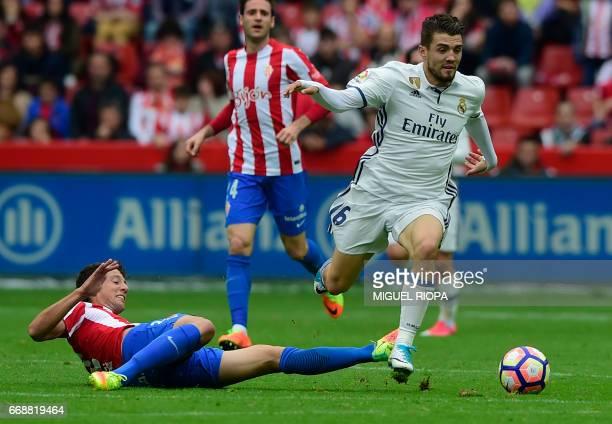 Real Madrid's Croatian midfielder Mateo Kovacic vies with Sporting Gijon's Croatian forward Duje Cop during the Spanish league football match Real...