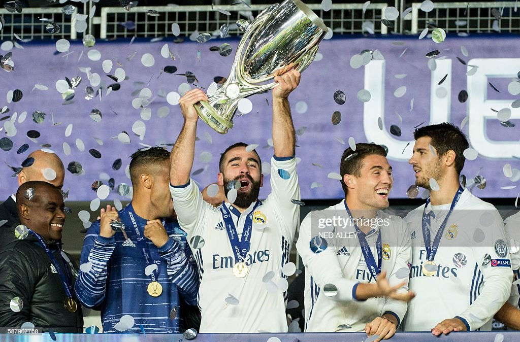 Real Madrid's Dani Carvajal (C) celebrates with the trophy after winning the UEFA Super Cup final football match between Real Madrid CF and Sevilla FC on August 9, 2016 at the Lerkendal Stadion in Trondheim. / AFP / NTB Scanpix / Ned ALLEY / Norway OUT
