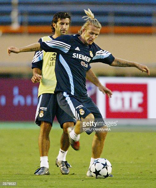 Real Madrid's David Beckham dribbles past Luis Figo during a team practice session at the National Stadium in Tokyo, 04 August 2003. Members of Real...
