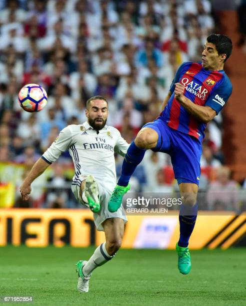 Real Madrid's defender Dani Carvajal vies with Barcelona's Uruguayan forward Luis Suarez during the Spanish league football match Real Madrid CF vs...