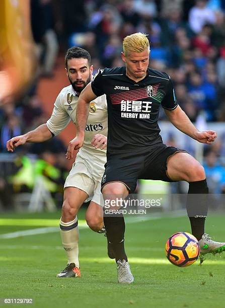Real Madrid's defender Dani Carvajal vies with Granada's French defender Franck Pascal Tabanou during the Spanish league football match Real Madrid...