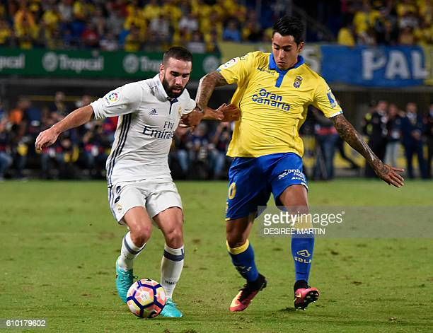 Real Madrid's defender Daniel Carvajal Ramos vies Las Palmas' Argentinian forward Sergio Araujo during the Spanish league football match UD Las...