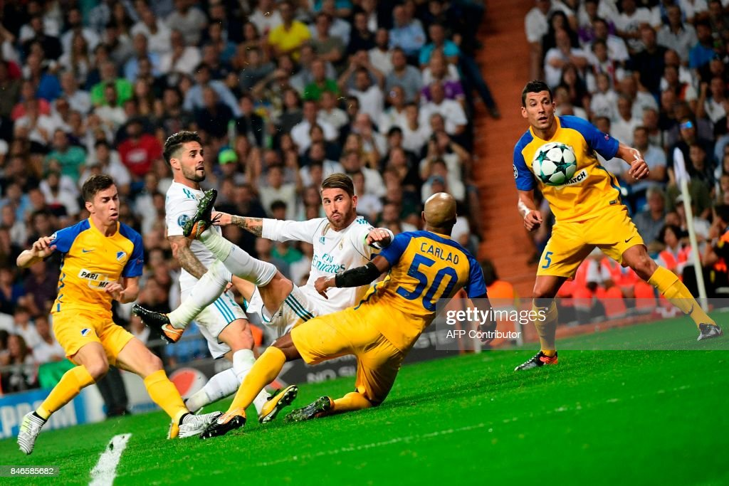 TOPSHOT - Real Madrid's defender from Spain Sergio Ramos (C) scores during the UEFA Champions League football match Real Madrid CF vs APOEL FC at the Santiago Bernabeu stadium in Madrid on September 13, 2017. /