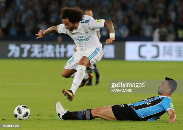 Real Madrid's defender Marcelo jumps to avoid a tackle by Gremio's Edilson during the Club World Cup UAE 2017 final football match between Gremio...