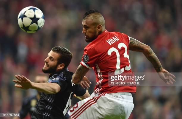 Real Madrid's defender Nacho Fernandez and Bayern Munich's Chilian midfielder Arturo Vidal vie for the ball during the UEFA Champions League 1st leg...