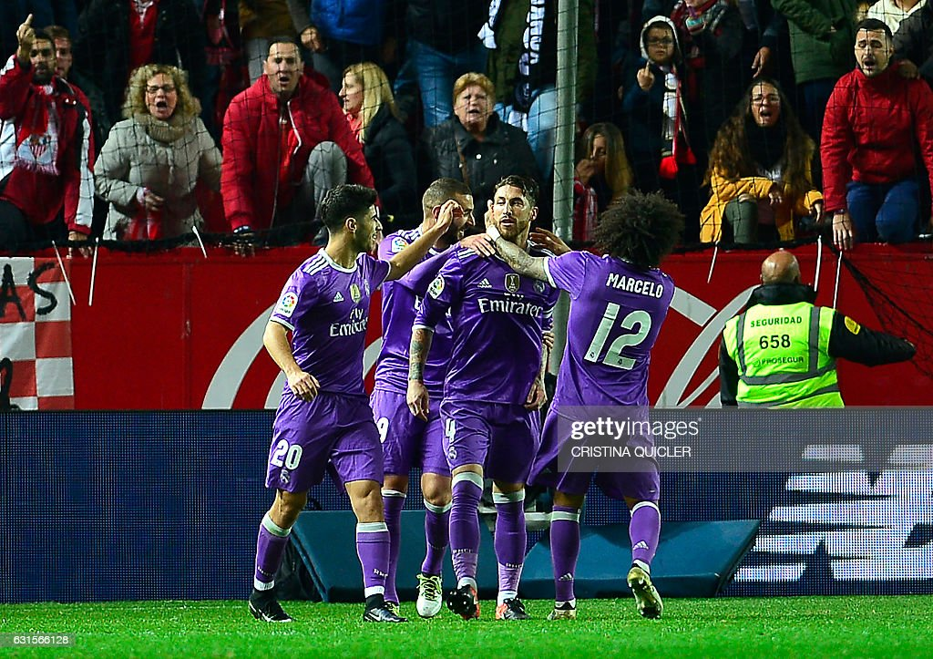 Real Madrid's defender Sergio Ramos (C) ceebrates with teammate after scoring a goal during the Spanish Copa del Rey (King's Cup) round of 16 second leg football match Sevilla FC vs Real Madrid CF at the Ramon Sanchez Pizjuan stadium in Sevilla on January 12, 2017. / AFP / CRISTINA