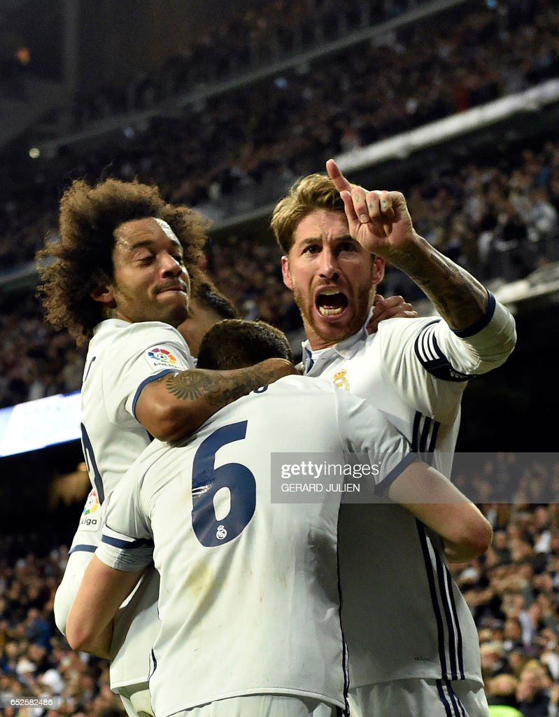 TOPSHOT - Real Madrid's defender Sergio Ramos (R) celebrates a goal with Real Madrid's Brazilian defender Marcelo (L) during the Spanish league footbal match Real Madrid CF vs Real Betis at the Santiago Bernabeu stadium in Madrid on March 12, 2017. /