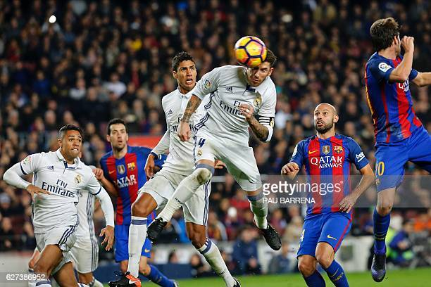TOPSHOT Real Madrid's defender Sergio Ramos heads a ball to score the equalizer past Real Madrid's French defender Raphael Varane and Barcelona's...