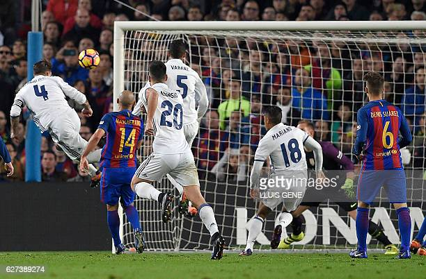Real Madrid's defender Sergio Ramos heads the ball to score a goal during the Spanish league football match FC Barcelona vs Real Madrid CF at the...