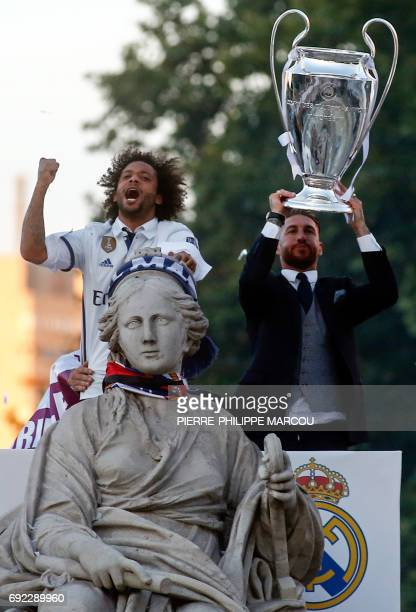 Real Madrid's defender Sergio Ramos holds up the trophy beside Real Madrid's Brazilian defender Marcelo celebrating the team's win on Plaza Cibeles...