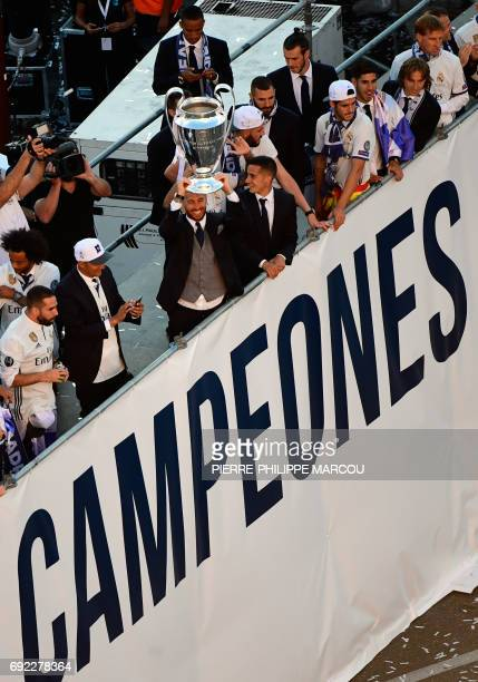 Real Madrid's defender Sergio Ramos holds up the trophy celebrating the team's win on Plaza Cibeles in Madrid on June 4 2017 after the UEFA Champions...