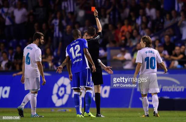 TOPSHOT Real Madrid's defender Sergio Ramos is shown a red card by the referee during the Spanish league footbal match RC Deportivo de la Coruna vs...