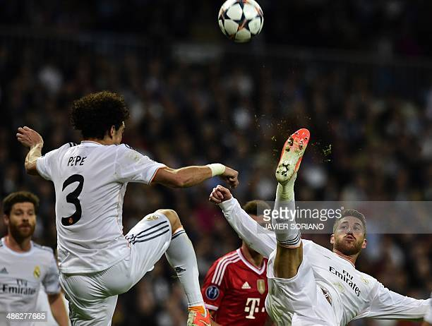 Real Madrid's defender Sergio Ramos jumps to kick the ball past Real Madrid's Portuguese defender Pepe during the UEFA Champions League semifinal...