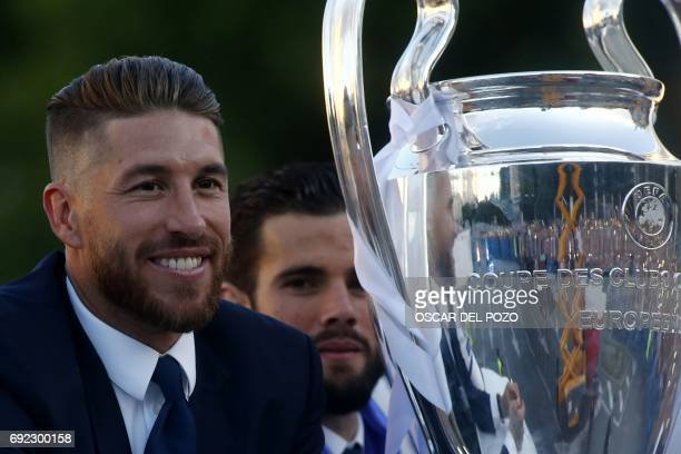 Real Madrid's defender Sergio Ramos smiles beside the trophy celebrating the team's win from an onpen decker bus on Plaza Cibeles in Madrid on June 4...