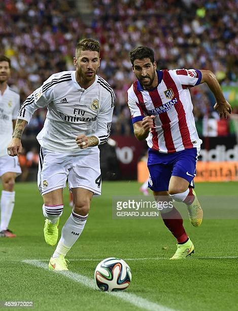 Real Madrid's defender Sergio Ramos vies with Atletico Madrid's midfielder Raul Garcia during the Spanish Supercopa secondleg football match Atletico...