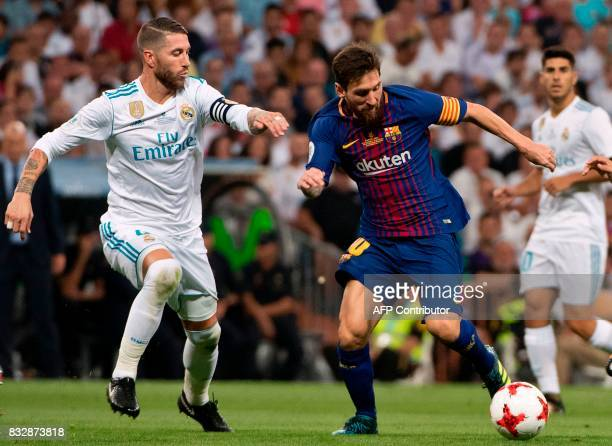 Real Madrid's defender Sergio Ramos vies with Barcelona's Argentinian forward Lionel Messi during the second leg of the Spanish Supercup football...