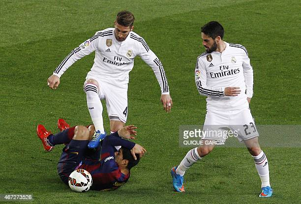 Real Madrid's defender Sergio Ramos vies with Barcelona's Uruguayan forward Luis Suarez as Real Madrid's midfielder Isco looks on during the clasico...