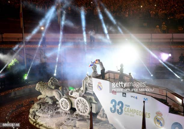 Real Madrid's defender Sergio Ramos waves a flag as he celebrates the team's win on the Cibeles fountain in Madrid on May 22 2017 after the the...