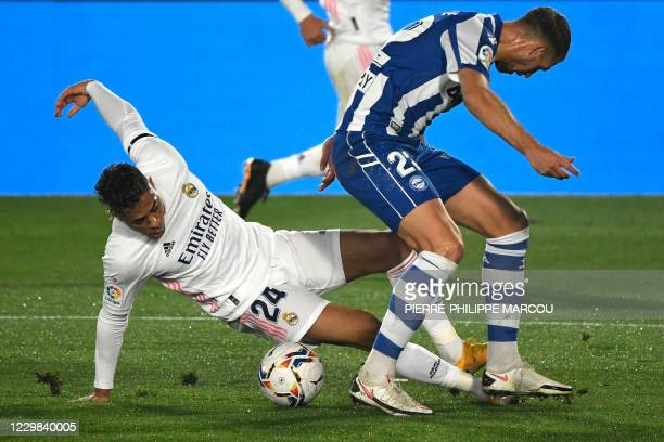 Real Madrid's Dominicans forward Mariano Diaz vies with Alaves' French defender Florian Lejeune during the Spanish League football match between Real...