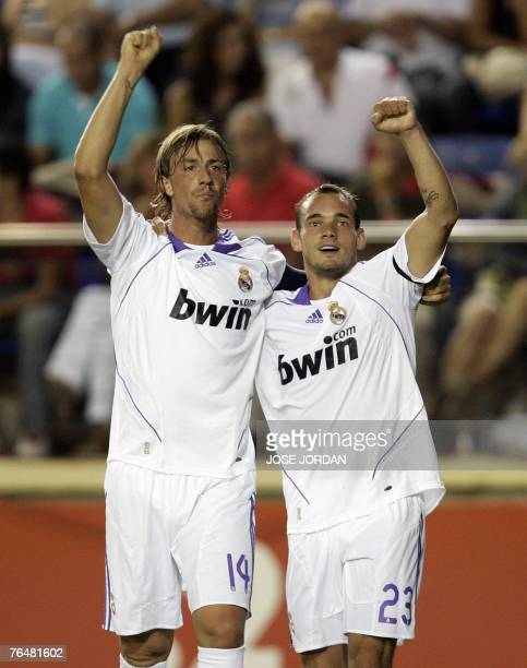 Real Madrid's Dutch Wesley Sneijder celebrates with Guti after scoring against Villarreal during a Spanish league match at the madrigal stadium in...