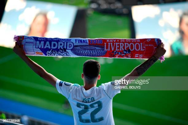 Real Madrid's fan wearing the jersey of Real Madrid's Spanish midfielder Isco brandishes a scarf prior to watch on a giant screen at the Santiago...