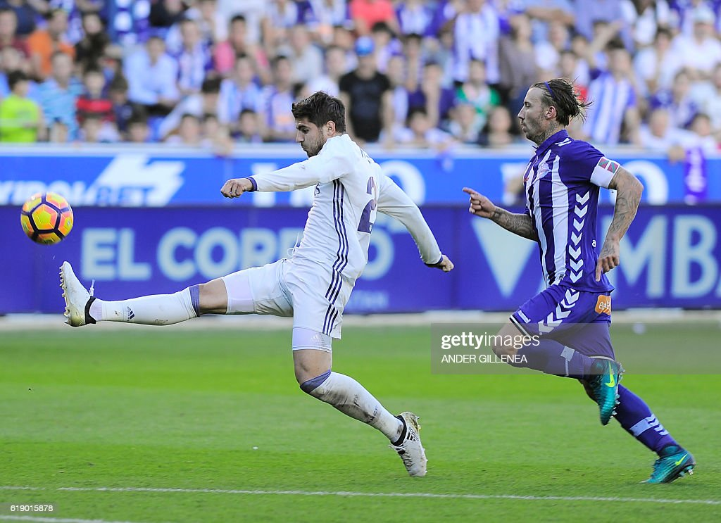 Real Madrid's forward Alvaro Borja Morata (L) kicks the ball to score a goal next to Deportivo Alaves' defender Alexis Ruano during the Spanish league football match between Deportivo Alaves and Real Madrid CF at the Mendizorroza stadium in Vitoria on October 29, 2016. / AFP / ANDER