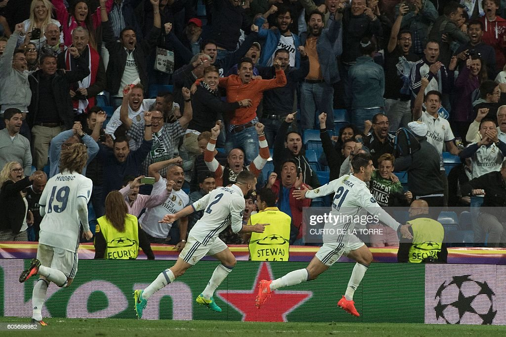 Real Madrid's forward Alvaro Morata (R) celebrates after scoring during the UEFA Champions League football match Real Madrid CF vs Sporting CP at the Santiago Bernabeu stadium in Madrid on September 14, 2016. / AFP / CURTO