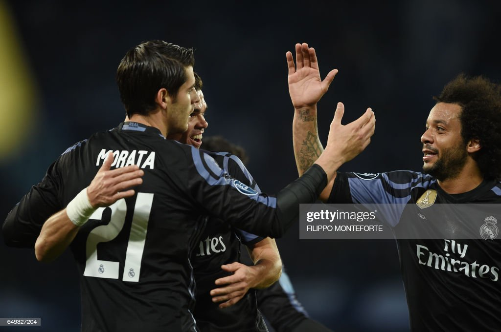 Real Madrid's forward Alvaro Morata (L) celebrates with teammates Real Madrid's Brazilian defender Marcelo (R) and Real Madrid's Portuguese defender Pepe after scoring at the end of the UEFA Champions League football match SSC Napoli vs Real Madrid on March 7, 2017 at the San Paolo stadium in Naples. Real Madrid won 1-3. / AFP PHOTO / Filippo MONTEFORTE