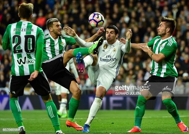 Real Madrid's forward Alvaro Morata vies with Betis' forward Dani Ceballos and Betis' Roumanian midfielder Alin Tosca during the Spanish league...