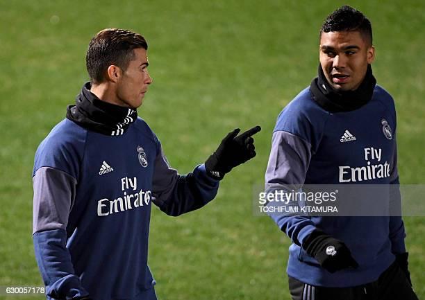 Real Madrid's forward Cristiano Ronaldo chats with midfielder Casemiro during a training session at Mitsuzawa stadium in Yokohama on December 16...
