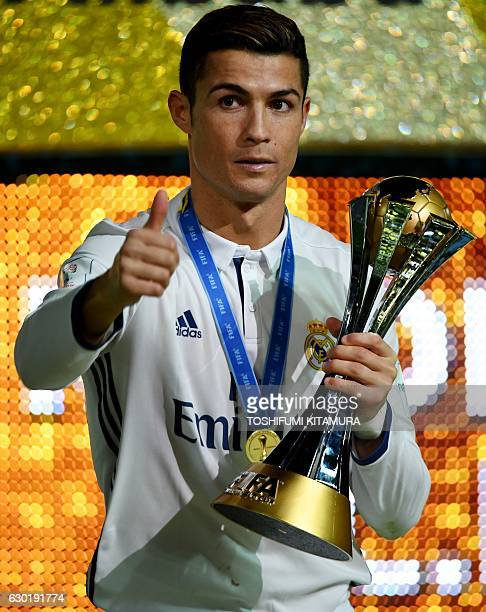 Real Madrid's forward Cristiano Ronaldo gives a thumbsup while holding the champion trophy on the podium after they won the Club World Cup football...