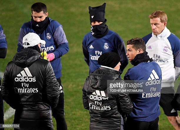 Real Madrid's forward Cristiano Ronaldo listens to head coach Zinedine Zidane with his teammates during a training session at Mitsuzawa stadium in...