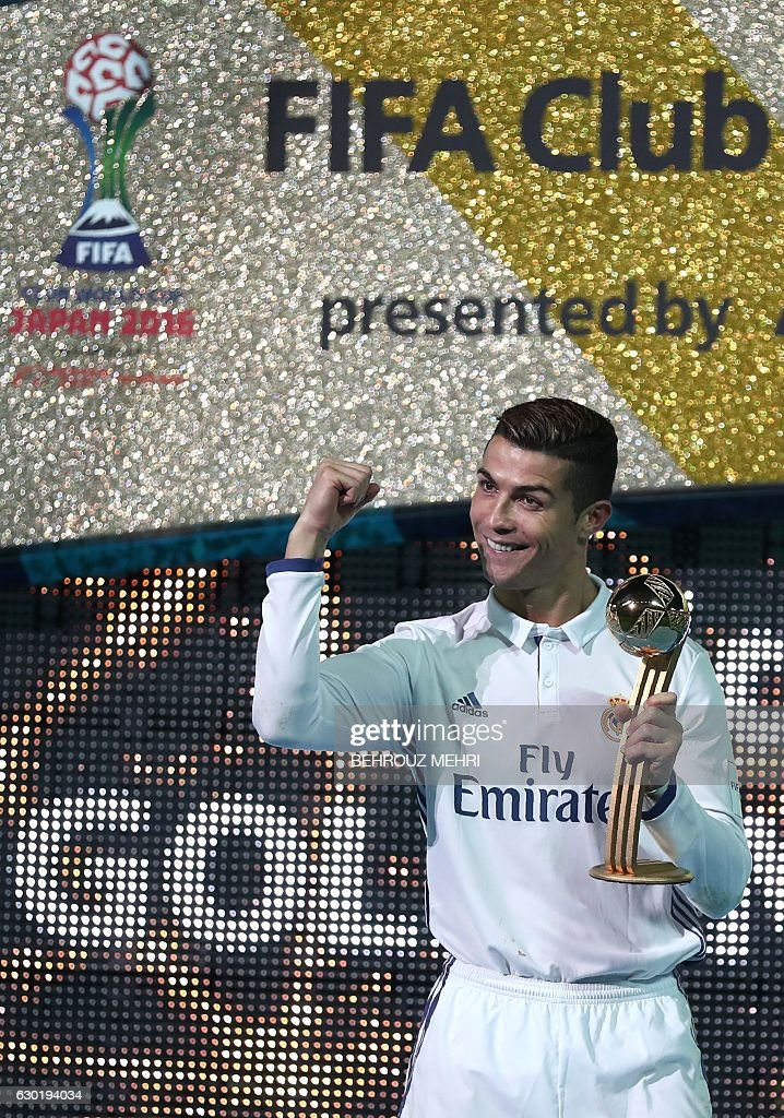 Real Madrid's forward Cristiano Ronaldo poses as he holds the Golden Ball trophy after winning the Club World Cup football final match between Kashima Antlers of Japan and Real Madrid of Spain at Yokohama International stadium in Yokohama on December 18, 2016. / AFP / Behrouz MEHRI