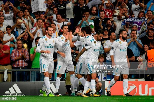 Real Madrid's forward from Portugal Cristiano Ronaldo celebrates with teammates after scoring during the UEFA Champions League football match Real...