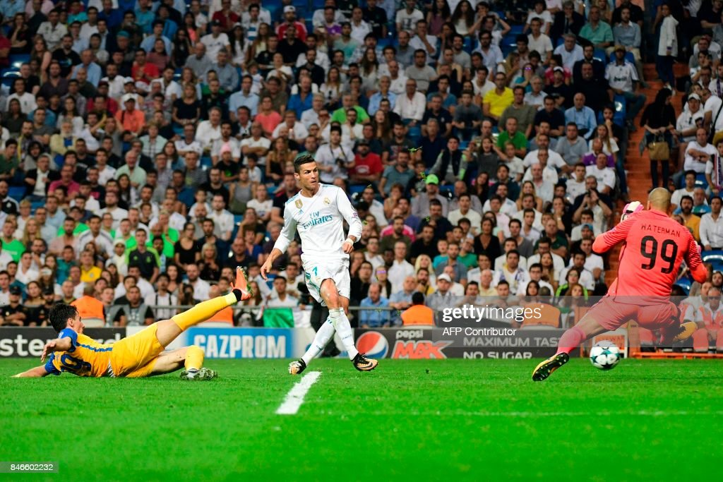 TOPSHOT - Real Madrid's forward from Portugal Cristiano Ronaldo (C) kicks the ball past APOEL Nicosia's goalkeeper from the Netherlands Boy Waterman during the UEFA Champions League football match Real Madrid CF vs APOEL FC at the Santiago Bernabeu stadium in Madrid on September 13, 2017. /