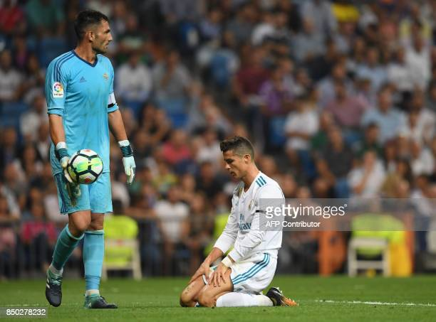 Real Madrid's forward from Portugal Cristiano Ronaldo kneels in front of Real Betis' goalkeeper from Spain Antonio Adan after missing a goal during...