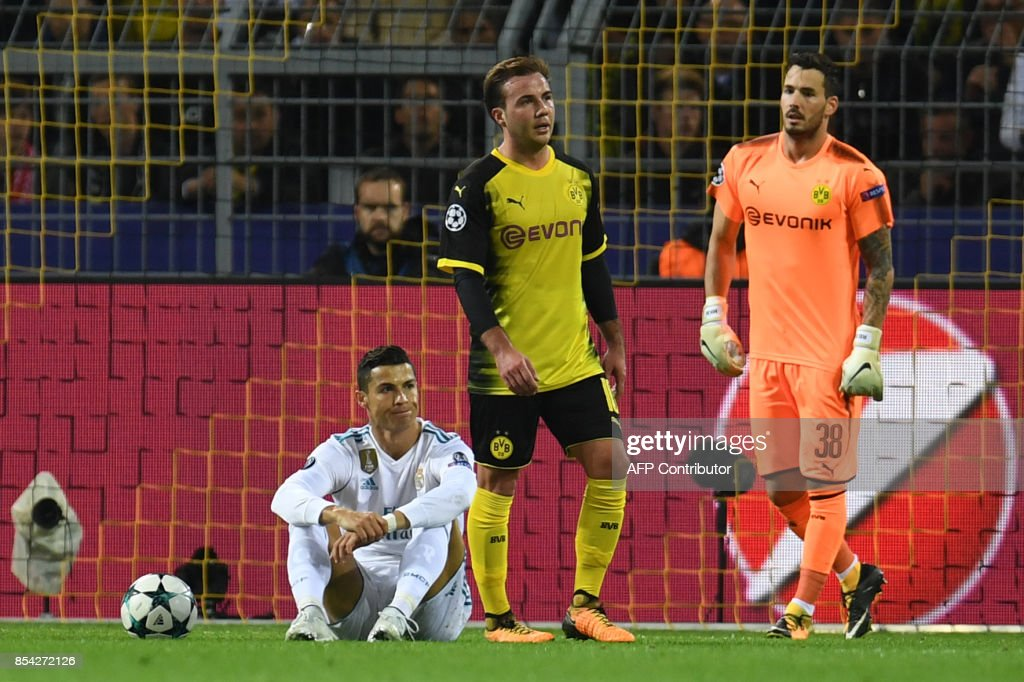 Real Madrid's forward from Portugal Cristiano Ronaldo (L) sits on the pitch in front of Dortmund's Swiss goalkeeper Roman Buerki's goal next to Dortmund's German midfielder Mario Goetze (C) during the UEFA Champions League Group H football match BVB Borussia Dortmund v Real Madrid in Dortmund, western Germany on September 26, 2017. / AFP PHOTO / Patrik STOLLARZ