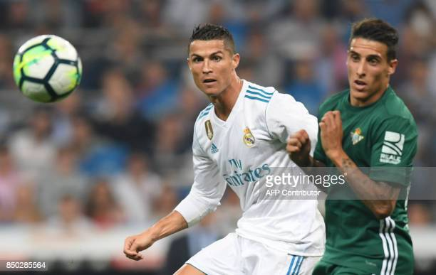Real Madrid's forward from Portugal Cristiano Ronaldo vies with during the Spanish league football match Real Madrid CF against Real Betis at the...