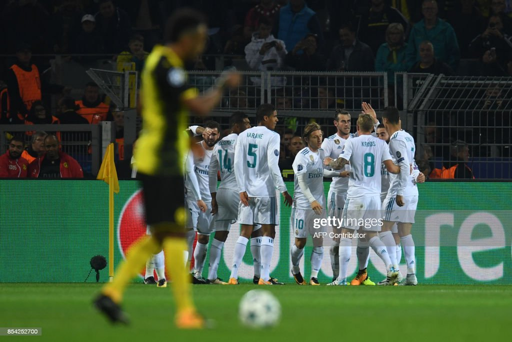 Real Madrid's forward from Wales Gareth Bale (4th R) celebrates scoring the opening goal with his teammates during the UEFA Champions League Group H football match BVB Borussia Dortmund v Real Madrid in Dortmund, western Germany on September 26, 2017. / AFP PHOTO / Patrik STOLLARZ