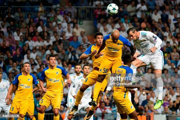 Real Madrid's forward from Wales Gareth Bale heads the ball past APOEL Nicosia's defender from Spain Roberto Lago APOEL Nicosia's midfielder from...