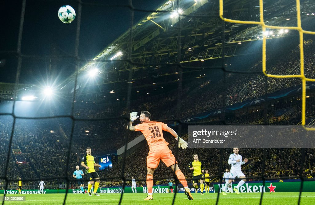 Real Madrid's forward from Wales Gareth Bale (R) scores the opening goal past Dortmund's Swiss goalkeeper Roman Buerki (C) during the UEFA Champions League Group H football match BVB Borussia Dortmund v Real Madrid in Dortmund, western Germany on September 26, 2017. / AFP PHOTO / Odd ANDERSEN
