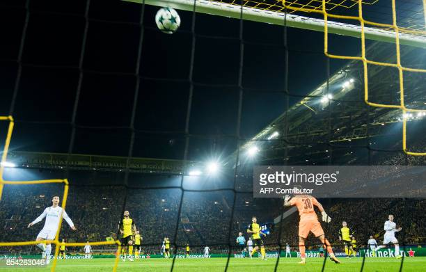 Real Madrid's forward from Wales Gareth Bale scores the opening goal past Dortmund's Swiss goalkeeper Roman Buerki during the UEFA Champions League...