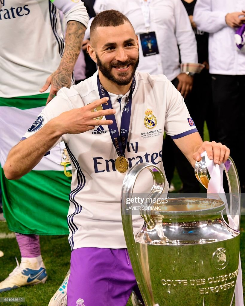 Real Madrid's forward Karim Benzema poses with the trophy after Real Madrid won the UEFA Champions League final football match between Juventus and Real Madrid at The Principality Stadium in Cardiff, south Wales, on June 3, 2017. /
