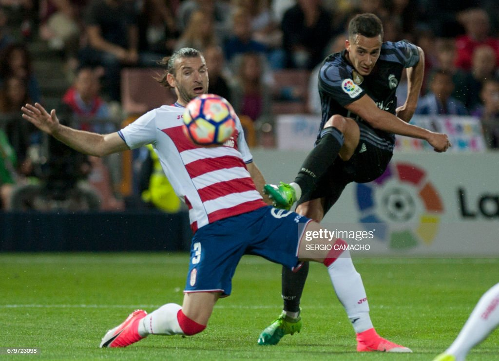 Real Madrid's forward Lucas Vazquez (R) shoots to score a goal beside Granada's Uruguayan defender Gaston Silva during the Spanish league football match Granada FC vs Real Madrid CF at Nuevo Los Carmenes stadium in Granada on May 6, 2017. /