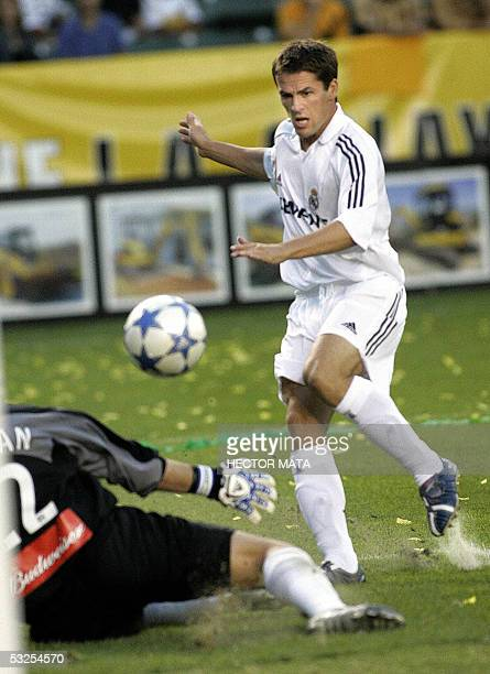 Real Madrid's forward Michael Owen passes the ball over Los Angeles Galaxy's goalkeeper Kevin Hartman to score the first goal during the first half...