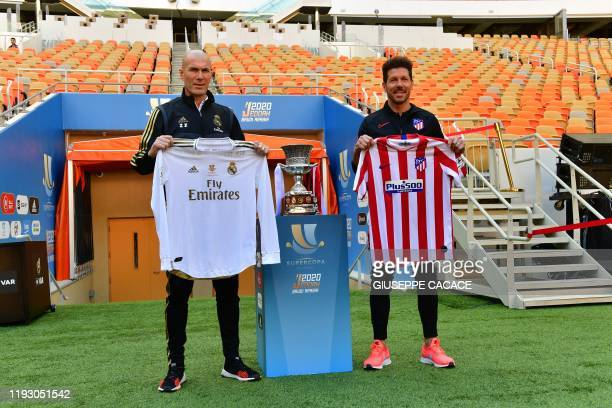 Real Madrid's French coach Zinedine Zidane and Atletico Madrid's Argentinian coach Diego Simeone carry their team's jersey as they pose next to the...