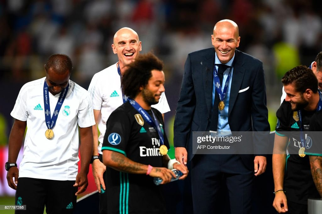 Real Madrid's French coach Zinedine Zidane (R) and his assistant David Bettoni (L) celebrate on the podium after winning the UEFA Super Cup football match between Real Madrid and Manchester United on August 8, 2017, at the Philip II Arena in Skopje. / AFP PHOTO / Dimitar DILKOFF